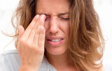 Una mujer joven se toca el ojo derecho inflamado con gesto de dolor