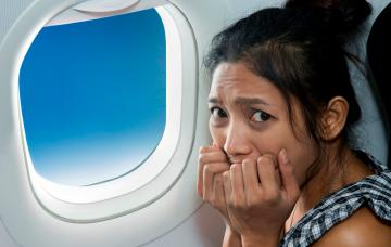 Mujer asustada en el interior de un avión