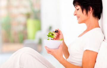 Una mujer de mediana edad lee un libro de recetas en la cocina