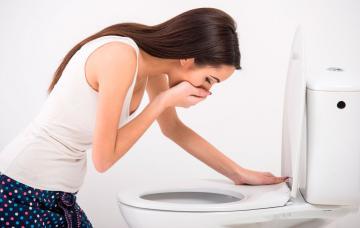 Mujer a punto de vomitar en el baño