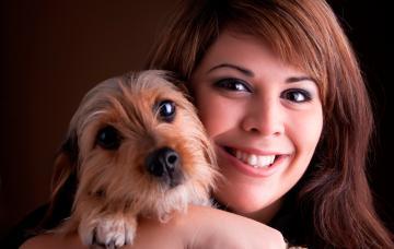 Una mujer posa sonriente con su perro en brazos