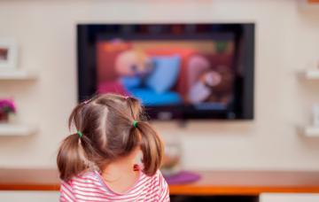 Niño pequeño junto a un televisor