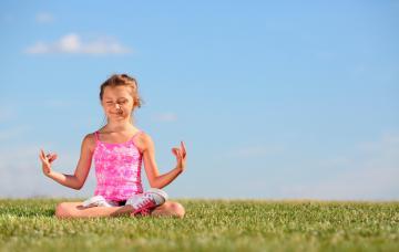Niña haciendo yoga al aire libre
