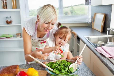 Madre jugando con su hija en la cocina