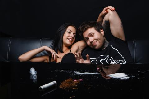 A young couple laughs after using cocaine