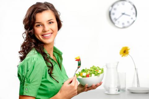 Mujer joven comiendo una ensalada