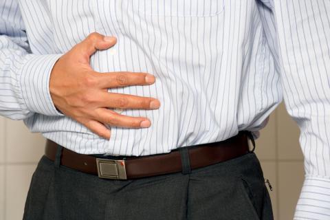 Hombre se toca el abdomen dolorido