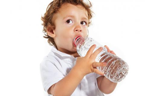 Un niño pequeño bebe agua de una botella