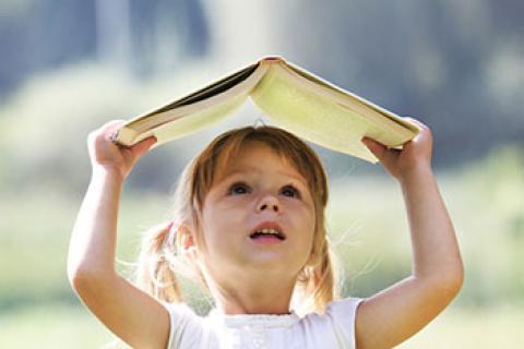 Una niña pequeña sujeta un libro sobre su cabeza