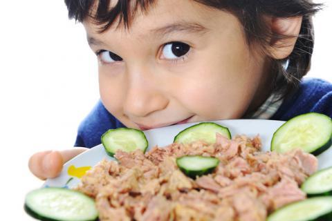 Niño con un plato de atún