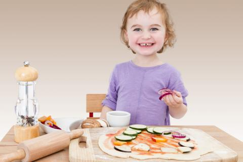 Niño junto a una pizza casera de verduras