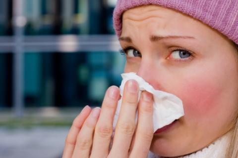 Mujer sonándose la nariz