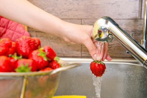 Una mujer lava higiénicamente unas fresas para preparar un plato