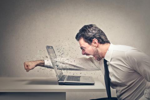 Hombre golpeando la pantalla del ordenador