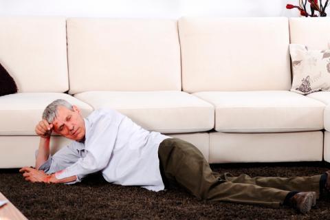 Un hombre caído junto al sofá en su casa