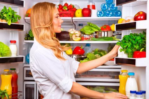 Mujer colocando los alimentos en la nevera