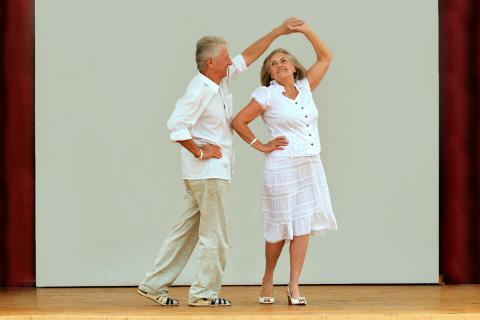 Una pareja de adultos mayores practicando bailes de salón