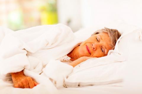 Una mujer mayor duerme en su cama