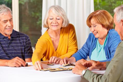 Un grupo de personas mayores juega al dominó
