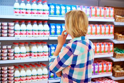 Mujer indecisa para comprar leche y lácteos