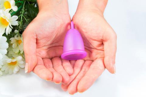 Manos de mujer sosteniendo una copa menstrual