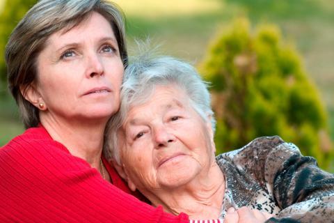 Una cuidadora abraza a una anciana en situación de dependencia