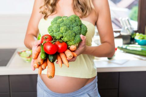 Mujer embarazada con verduras y hortalizas