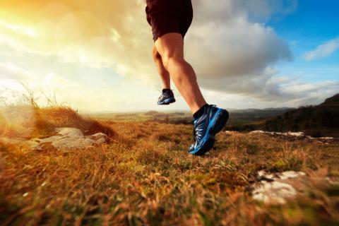 Piernas de un hombre corriendo por el campo