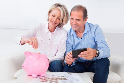 Una pareja mayor guarda dinero en una hucha