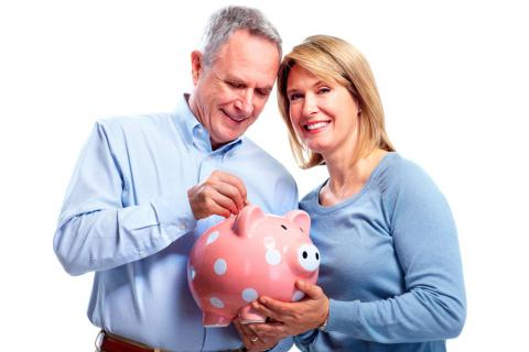 Una pareja de mediana edad guarda dinero en una hucha