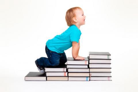 Niño apoyado sobre una escalera hecha con libros