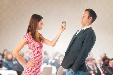 Una mujer muestra un anillo de compromiso a un hombre que se inclina hacia atrás