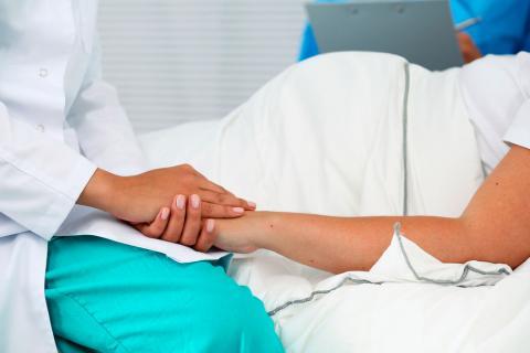 Una obstetra coge de la mano a una embarazada