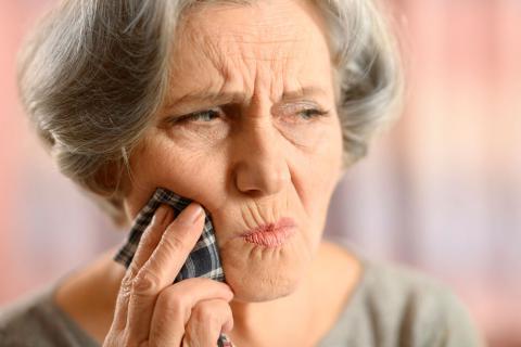 Una mujer mayor se toca la mejilla dolorida
