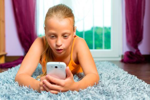 Una niña consulta su smartphone tumbada en su cama