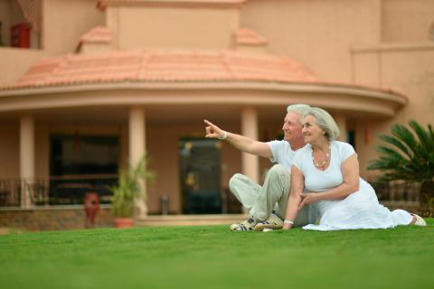 Pareja de adultos mayores sentados en el césped del jardín de un senior resort
