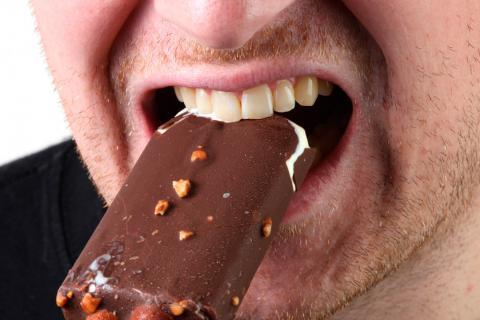 Hombre mordiendo un bombón helado