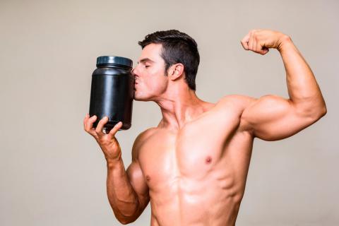 Hombre besando un bote de suplementos pre-workout