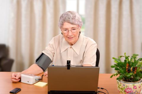 Una anciana se toma la tensión en casa frente a la pantalla de un ordenador