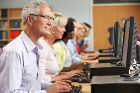 Grupo de personas de mediana edad en un aula con ordenadores