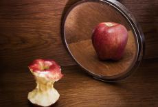 Manzana mordida se refleja en el espejo como una entera