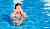 Una joven en la piscina se frota los ojos