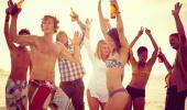 Grupo de personas en la playa bebiendo alcohol