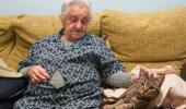 Una anciana sentada en un sofá acaricia a un gato