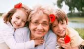 Una abuela posa sonriente con sus dos nietos
