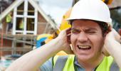 Un obrero de la construcción se tapa los oídos para protegerse de un ruido intenso