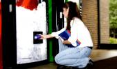 Jóven comprando bebida de máquina expendedora