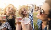 Tres chicas muy sonrientes en un parque sostienen vasos de cerveza