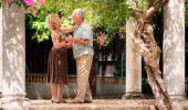 Dos adultos mayores bailan en un jardín