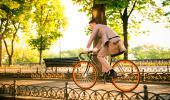 Un hombre pasea en bicicleta por un parque